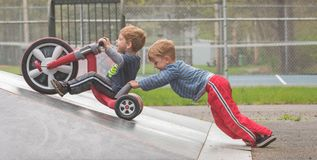 Two Boys Cooperating in Play. Two young boys playing and riding a big wheel in a skate park cooperating with one another stock images
