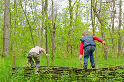 Two young boys playing on a rustic fence Royalty Free Stock Image