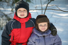 Two Young Boys Playing in Snow. Two young boys, both brothers, warmly dressed for a day outdoors, playing in the winter snow Royalty Free Stock Photos