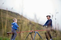 Two young boys playing on a teeter totter stock image