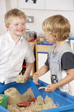 Two Young Boys Playing Together in Sandpit  Royalty Free Stock Images