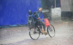 Two young boys riding a bicycle in the rain royalty free stock photos