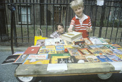 Two young boys selling books Stock Images