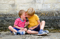 Two young boys sharing a lollipop Royalty Free Stock Photo
