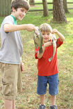 Two young boys showing off their catch Stock Photography
