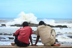 Two boys lost in their own thought, Kanyakumari. Two young boys sitting near the beach, lost in their own deep thought while a huge wave is crashing against a Stock Images