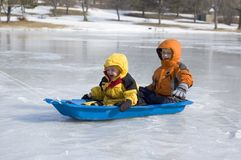 Two Young Boys Sled on Icy Lake. Two cute laughing young boys ride a sled over an ice covered lake Royalty Free Stock Image