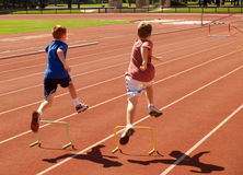 Two young boys with small hurdles. Two young boys leaping over small hurdles Stock Photography