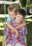 Two young boys on a swing. Two young boys posing on a garden swing Royalty Free Stock Image