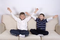 Two Young Boys Victory!. Two young boys sitting on a couch with their hands in the air displaying victory. White background, but not isolated Stock Images