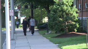 Two young boys walking down the sidewalk. A view or scene from around town stock video