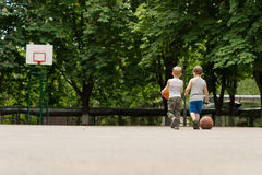 Two young boys walking off a basketball court Stock Image