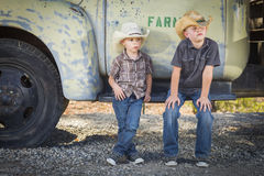 Two Young Boys Wearing Cowboy Hats Leaning Against Antique Truck Stock Photo