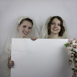 Two young brides holding blank sign Stock Photography