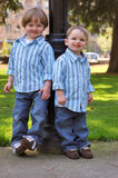 Two Young Brothers. Outdoors shot of two young brothers wearing identical button-up shirts and blue jeans Stock Photography