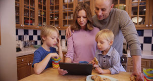 Two young brothers eating cookies and watching a tablet with par Royalty Free Stock Image