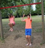 Two young brothers jump and do workout. In an outdoor gym stock images