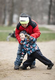 Two young brothers playing outdoors in winter Stock Images