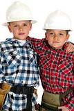 Two young brothers wearing hardhats and tool belts Stock Photos