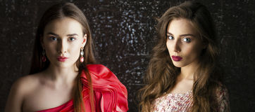 Two Young brunette women on dark studio wall background Royalty Free Stock Photography