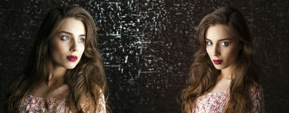 Two Young brunette women on dark studio wall background Royalty Free Stock Photo