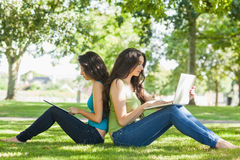 Two young brunette women sitting on a lawn Royalty Free Stock Images