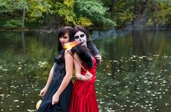 Two brunettes women with makeup like a Halloween skull and Hallo. Two young brunettes women with makeup like a Halloween skull and Halloween witch makeup stands Royalty Free Stock Image