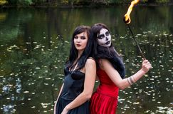Two young brunettes women with makeup like a Halloween skull and. Halloween witch makeup stands with a torch in a red and black dresses in front of the autumn Royalty Free Stock Images