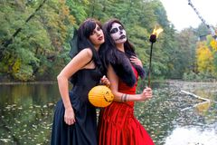 Two young brunettes women with makeup like a Halloween skull and. Halloween witch makeup stands with a torch in a red and black dresses in front of the autumn Royalty Free Stock Image