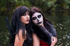 Two young brunettes women with makeup like a Halloween skull and. Halloween witch makeup stands in a red and black dresses in front of the autumn lake Royalty Free Stock Image