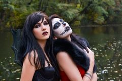 Two young brunettes women with makeup like a Halloween skull and. Halloween witch makeup stands in a red and black dresses in front of the autumn lake Stock Photos
