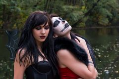 Two young brunettes women with makeup like a Halloween skull and. Halloween witch makeup stands in a red and black dresses in front of the autumn lake Stock Image