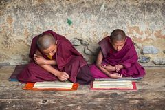 Two Himalayan Bhutanese young novice monks sitting on floor and chanting , Bhutan. These two young Buddhist novice monks reading and chanting . boys would stock photography