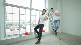 Two young builders standing at the ladder. Good job.Two young builders standing at the ladder with paint cans in hand showing thumbs up stock footage