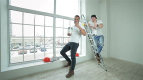 Two young builders standing showing thumbs up. Moving and repairs in the apartment.Two young builders standing at the ladder with paint cans in hand showing stock footage