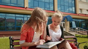 Two young business girls on the bench working with papers on background of office building. stock video footage