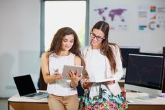 Two young business girls are examining documents and a tablet Royalty Free Stock Images