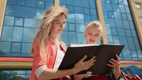 Two young business girls working with papers on background of office building. stock video footage