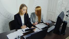 Two young business ladies in strict business suits work in the office, sit at the table, look at the tablet.  stock video footage
