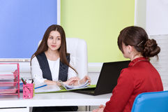 Two young business lady negotiate. Royalty Free Stock Image