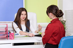 Two young business lady negotiate. Stock Images