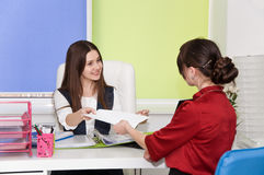 Two young business lady negotiate. Royalty Free Stock Photography