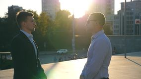 Two young business men standing outdoor at city square and talking. Businessmen meet and speaking outside with cityscape. At background. Communication of happy stock video