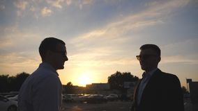 Two young business men standing outdoor near parking and talking. Businessmen meet and speaking outside in the city with. Sunset at background. Communication of stock video footage