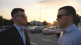 Two young business men standing outdoor near parking and talking. Profile of businessmen in sunglasses speaking outside. In the city. Communication of happy stock footage