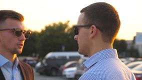 Two young business men standing outdoor and talking. Businessmen in sunglasses meet and speaking outside in the city. Communication of serious colleagues in stock footage