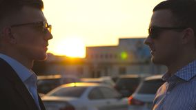 Two young business men standing outdoor and talking. Businessmen in sunglasses meet and speaking outside in the city. With sun flare at background stock footage