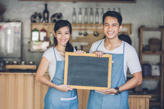 Two young business partner open their cafe. Portrait of two young business partner open their coffe shop. standing with blank blackboard sign Stock Photo