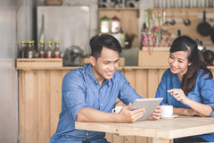 Two young business partner using tablet together. Portrait of two young business partner using tablet together in the cafe Royalty Free Stock Images