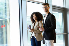 Two young business partners looking at camera in a hallway of the company. Stock Image